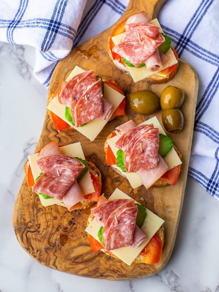 ham and salami tea sandwiches on olive board