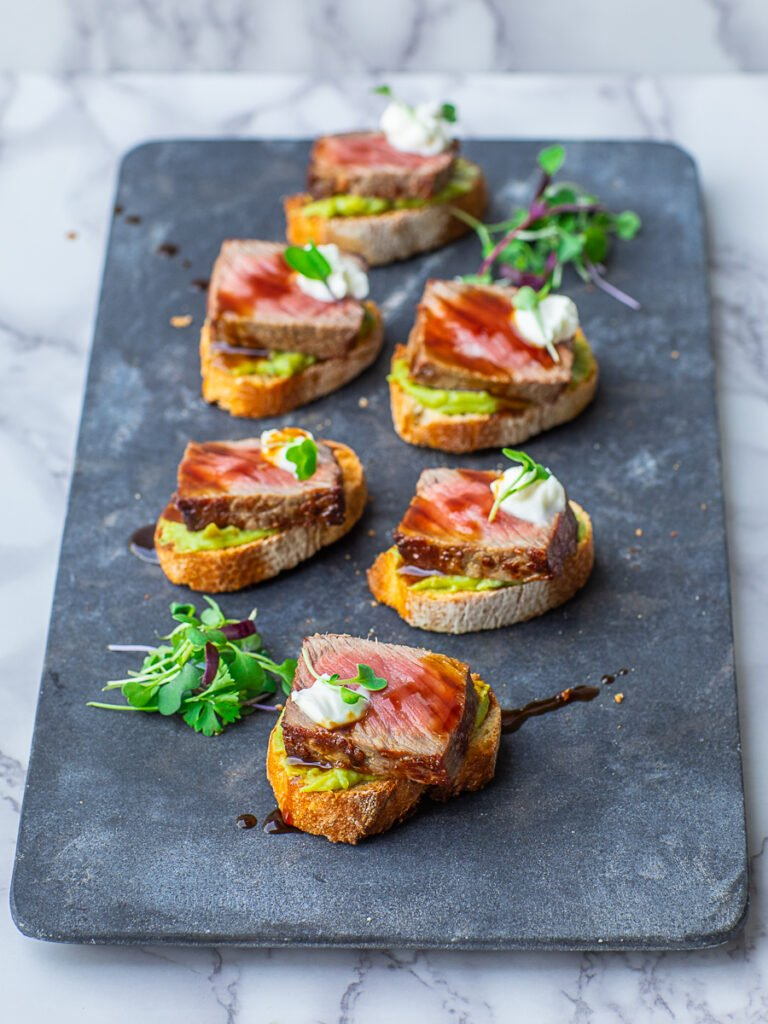 guacamole steak crostini with steak sauce