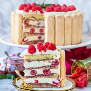 sliced raspberry tiramisu cake with fresh berries and ladyfinger cookies