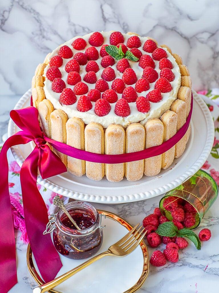 raspberry cake garnished with fresh raspberries and ladyfinger cookies