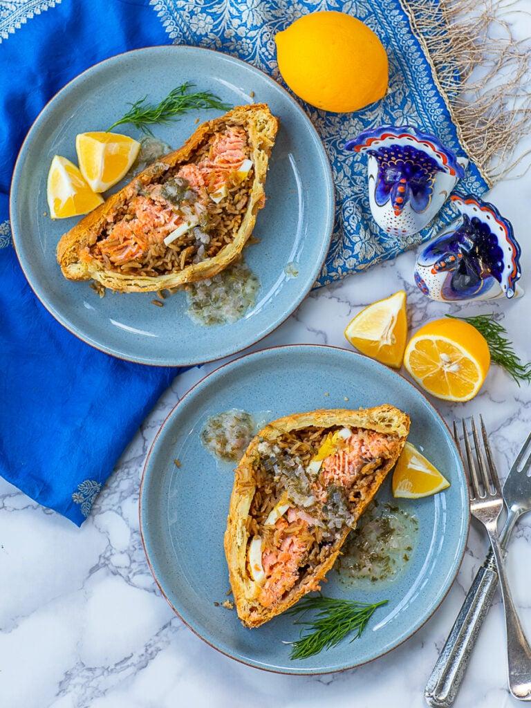 salmon coulibiac slices with mushroom rice, eggs, sauce and lemons