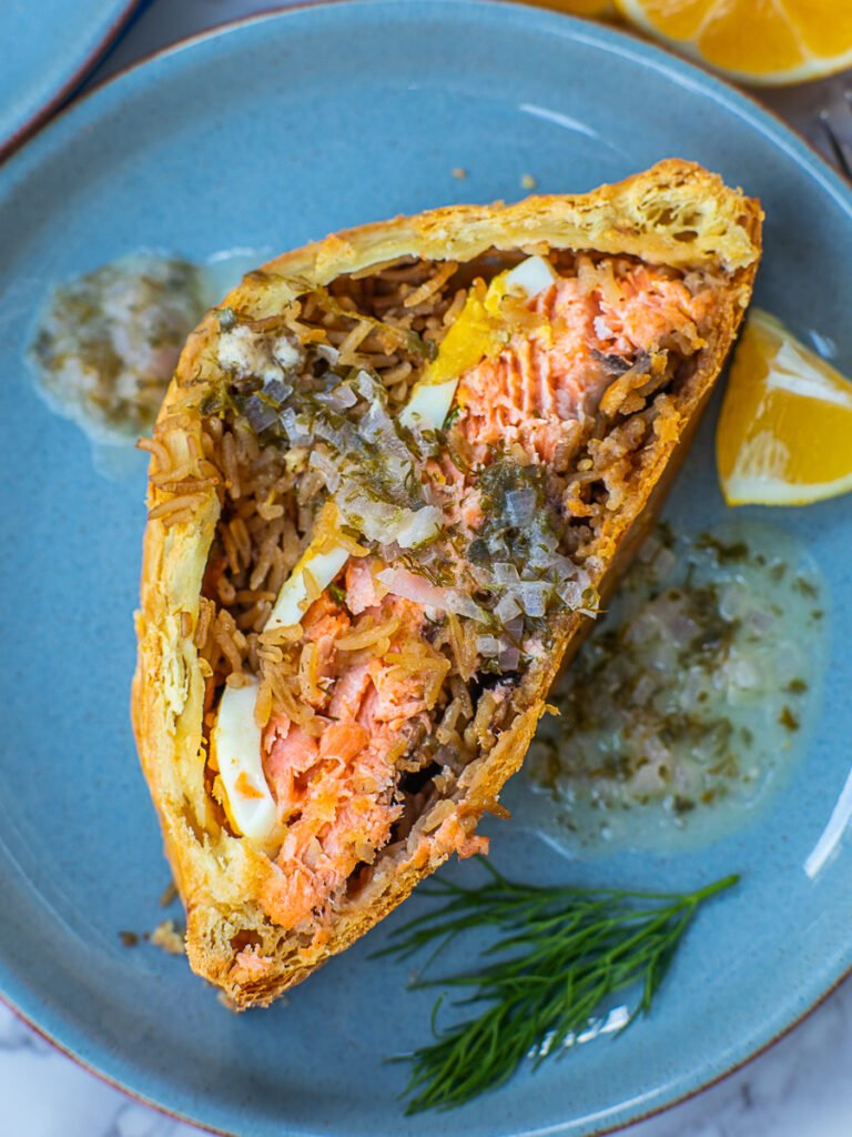 slice of salmon coulibiac with sauce; Russian seafood recipe