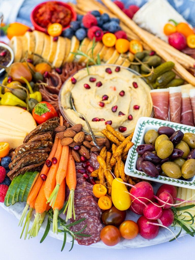 cheese board with salami, veggies and hummus