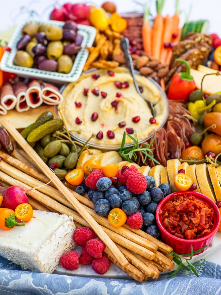 holiday cheese board with berries, olives and hummus