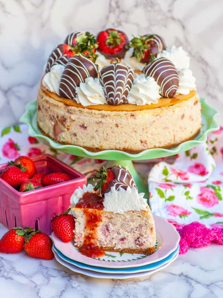 strawberry cheesecake sliced with chocolate strawberries and whipped cream