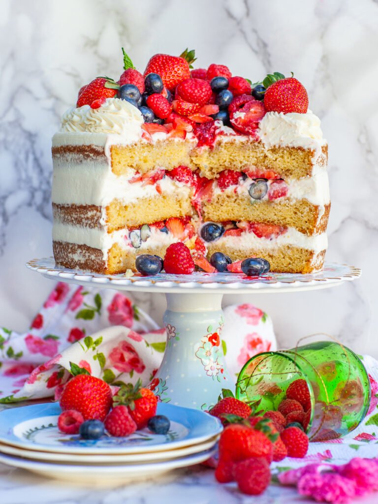 inside look of berry cake with whipped cream and berries