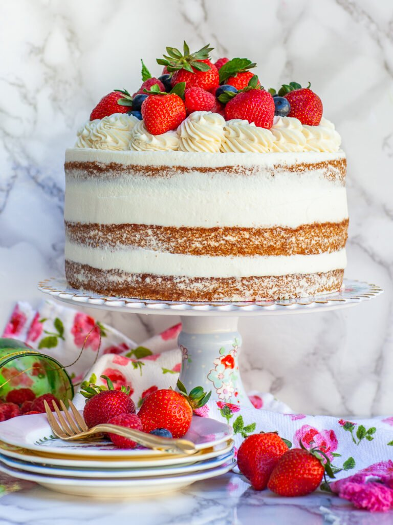 naked style berry cake with mascarpone whipped cream frosting, topped with berries