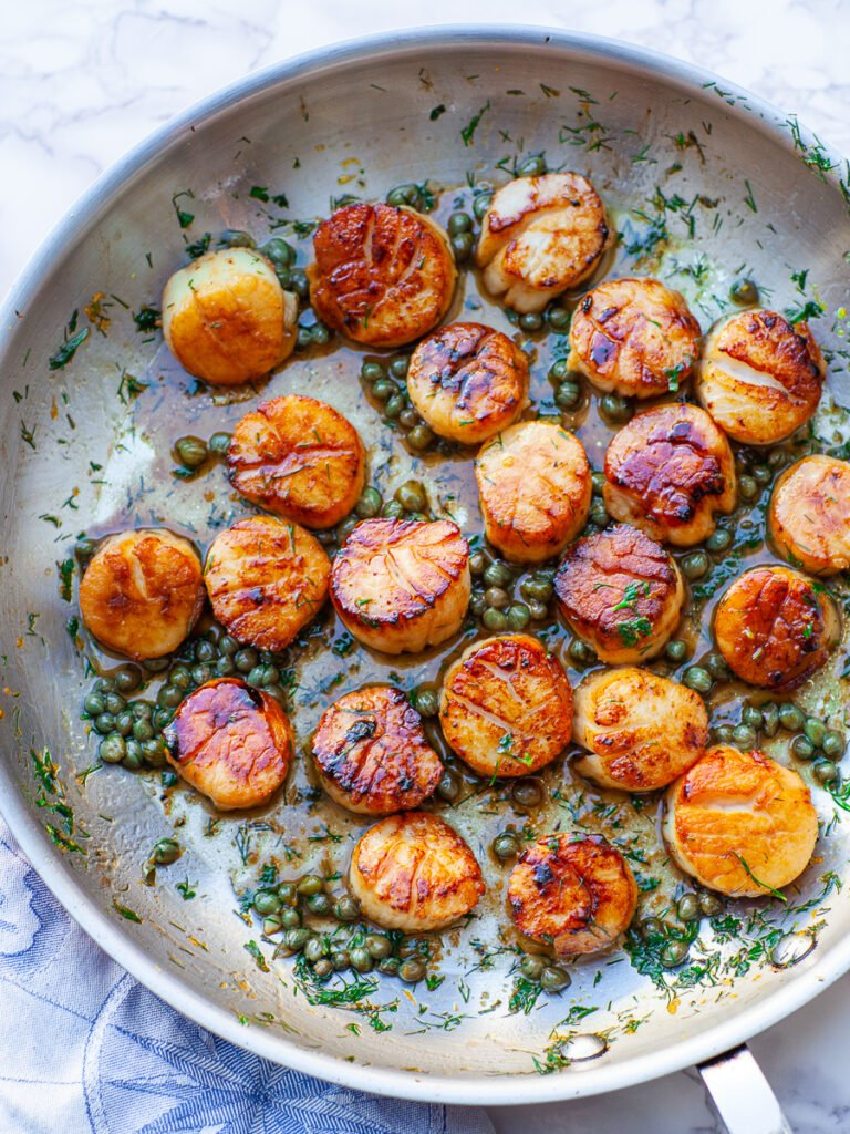 pan-seared scallops in large frying pan with capers and dill