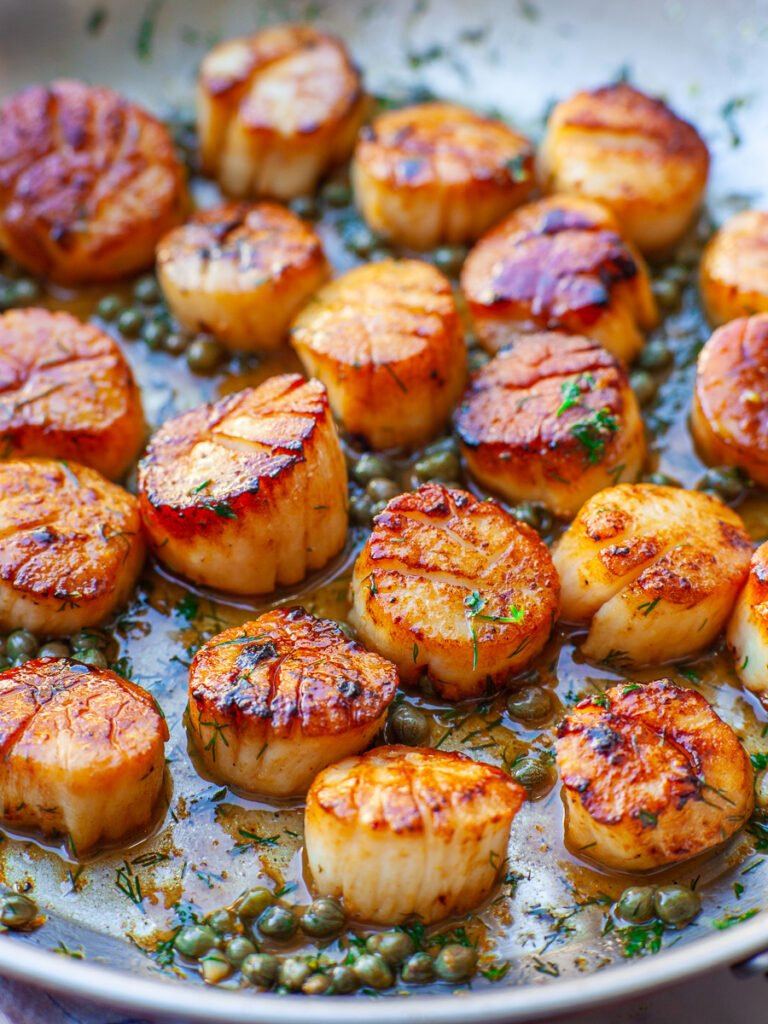 close up of pan-seared scallops with capers and sauce