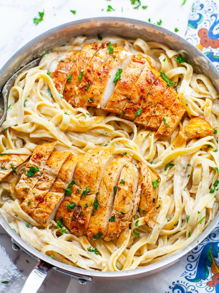 garlic chicken breast over fettuccine alfredo in pan