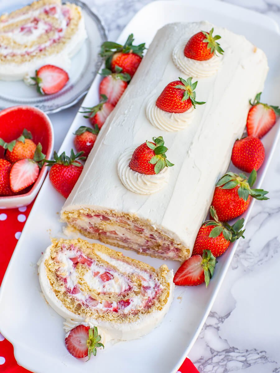 overhead view of strawberry cake with fresh strawberries and whipped cream frosting