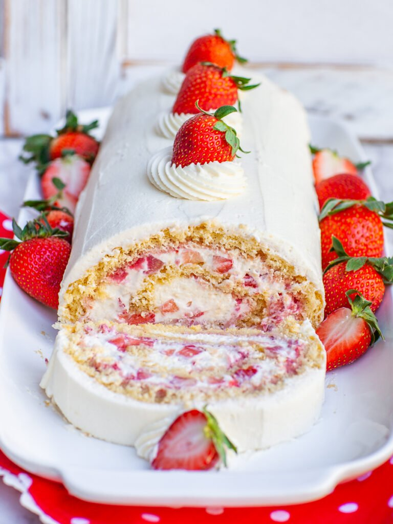strawberry swiss roll cake with whipped cream and fresh berries