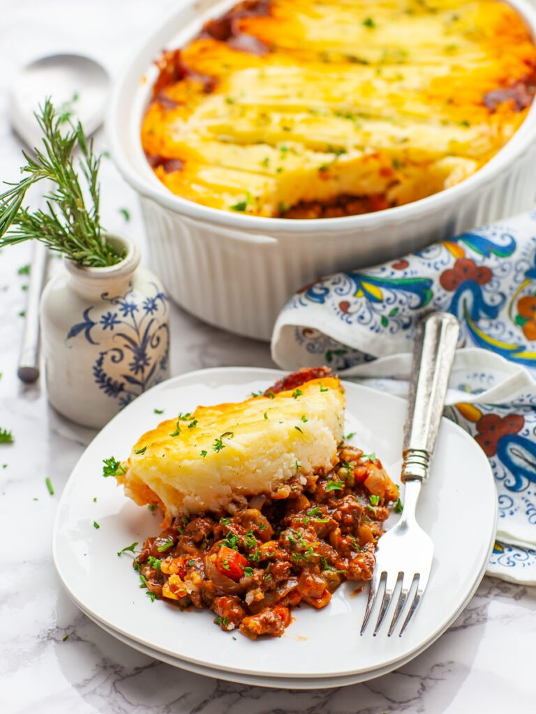 shepherd's pie on a plate, garnished with fresh parlsey