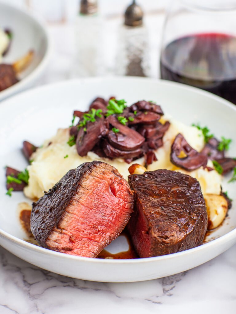 filet mignon steak dinner with potatoes, mushrooms and red wine