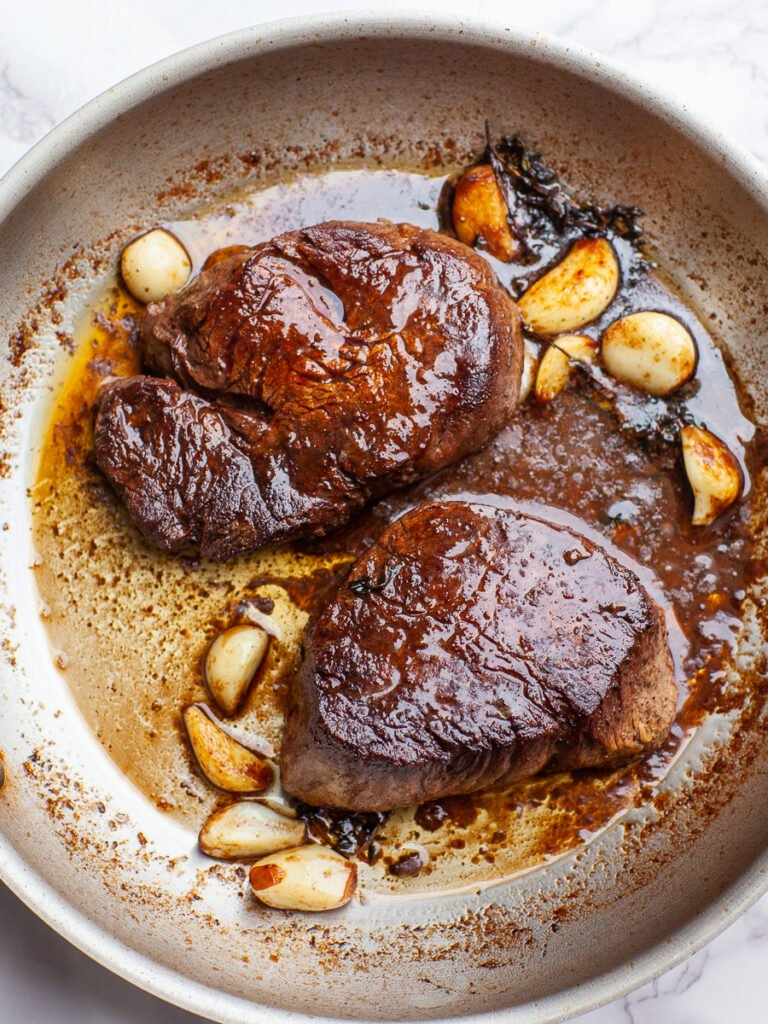 filet mignon steaks in frying pan with garlic, sauce and thyme
