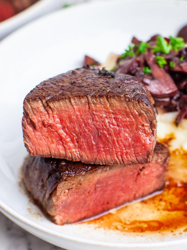 close up of medium rare steak with pan sauce