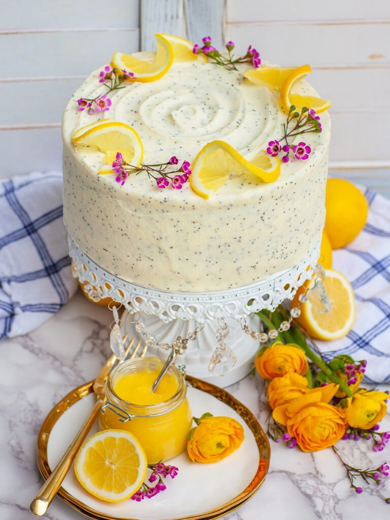 lemon poppy seed cake with poppy seed cream cheese frosting, garnished with flowers and lemon
