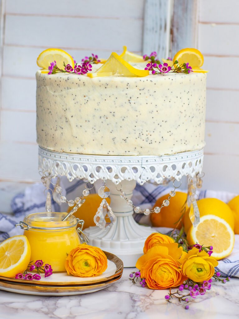 lemon poppy seed cake with lemons and flowers on white crystal stand