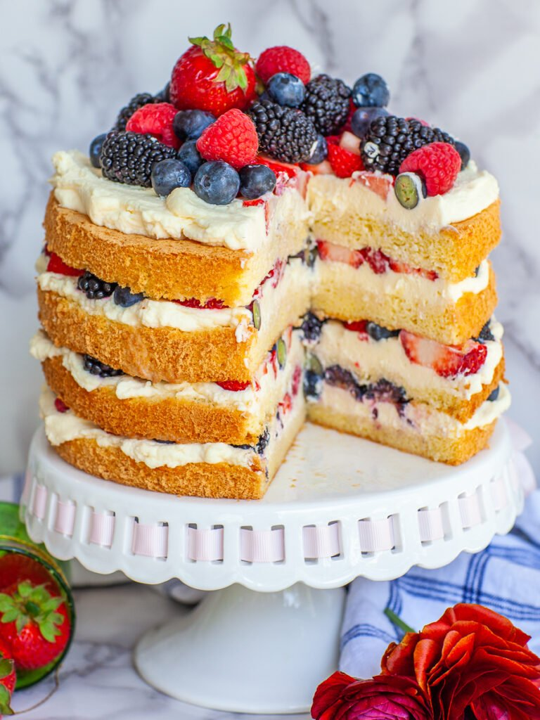 sliced berry cake with sponge cake layers and whipped cream frosting