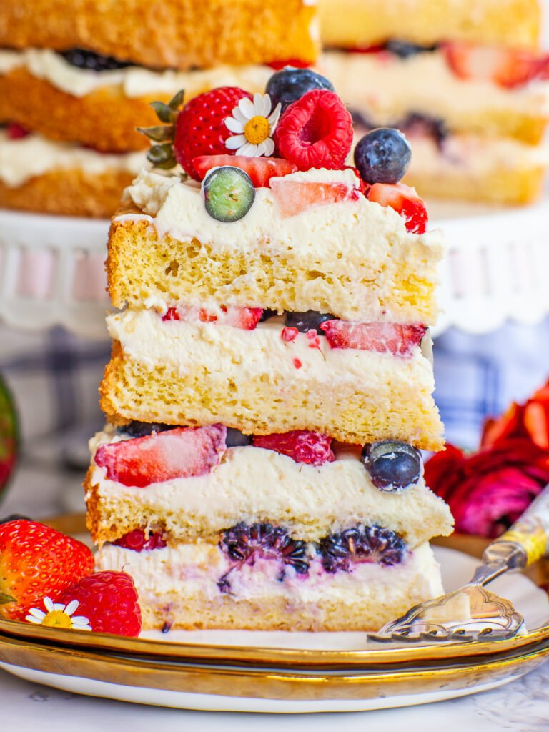 close up slice of berry tres leches cake, with mascarpone frosting