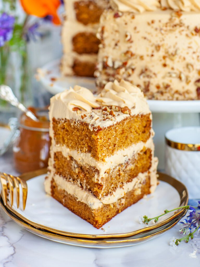 close up slice of caramel cake with diced pecans and whipped cream frosting