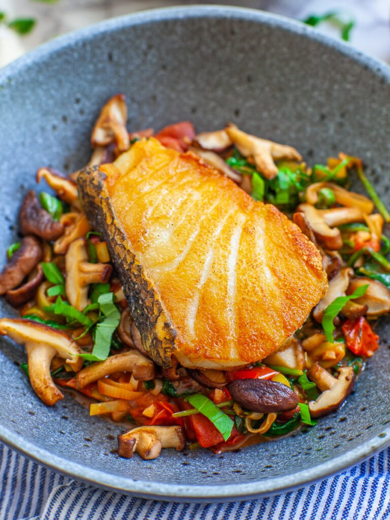 fried wild sea bass over a bed of mushrooms and spinach