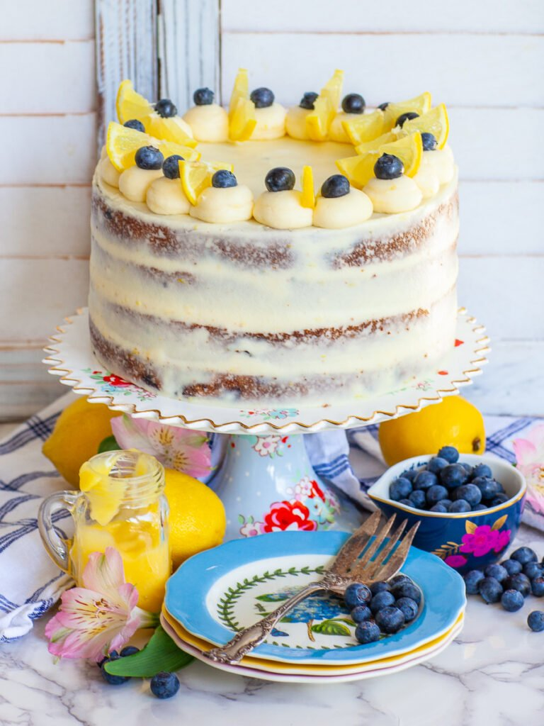 blueberry cake with cream cheese frosting, garnished with lemon wedges and berries