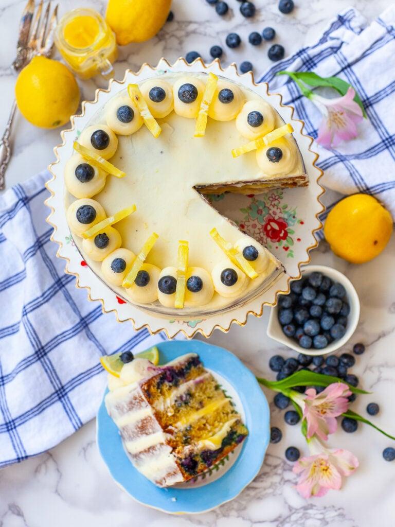 sliced blueberry lemon cake, with berries and lemons