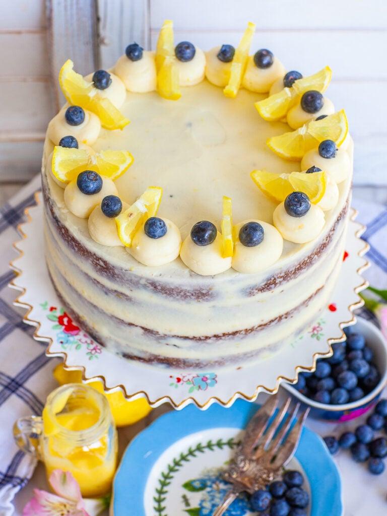 lemon blueberry cake garnished with berries and lemon wedges