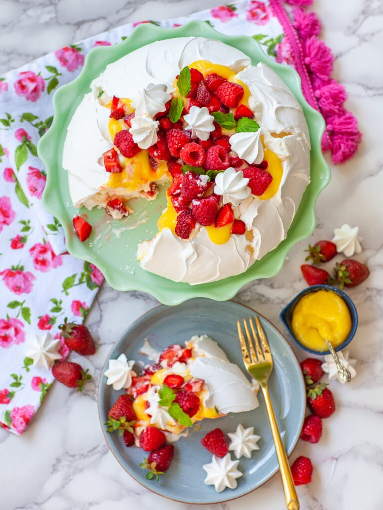 classic pavlova served with whipped cream, lemon curd and berry topping