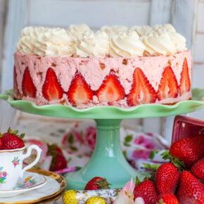 rhubarb strawberry cheesecake with strawberry garnish and whipped cream