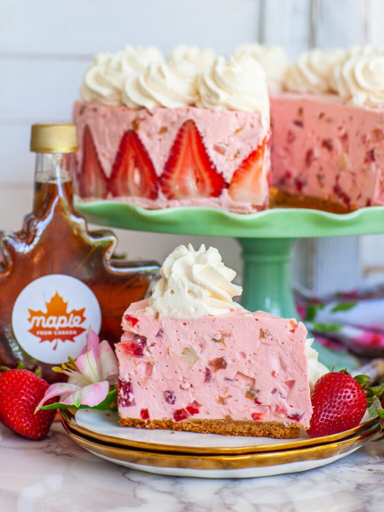 slice of strawberry cheesecake, with whipped cream and maple syrup