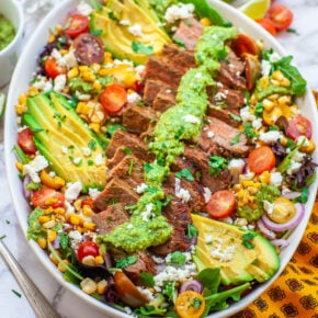 grilled steak salad with avocado, corn, cheese and chimichurri dressing