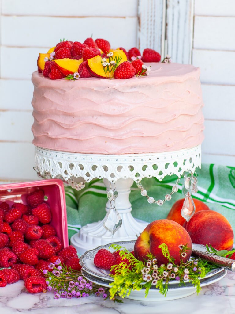 peach raspberry cake topped with berries and fruit