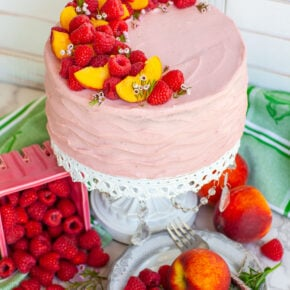 raspberry peach cake with raspberry frosting, with raspberries and peaches