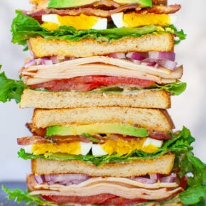 stacked BLT club sandwich with eggs, avocado, bacon, ham, cheese, tomatoes and lettuce