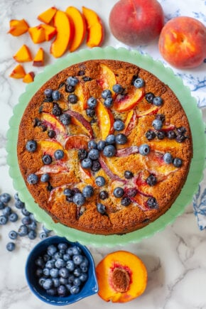 ricotta cake topped with sliced peaches and blueberries