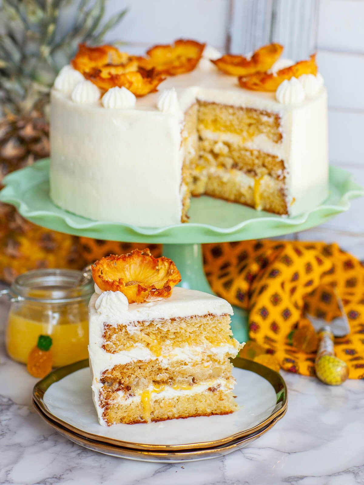 sliced pineapple cake on cake stand and cake slice on plate